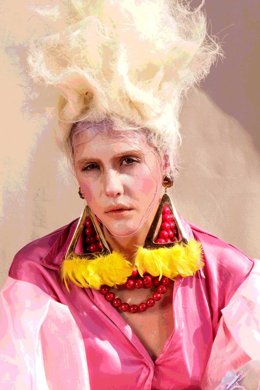 Blond kvinne med gule trekantede øredobber og rosa bluse.