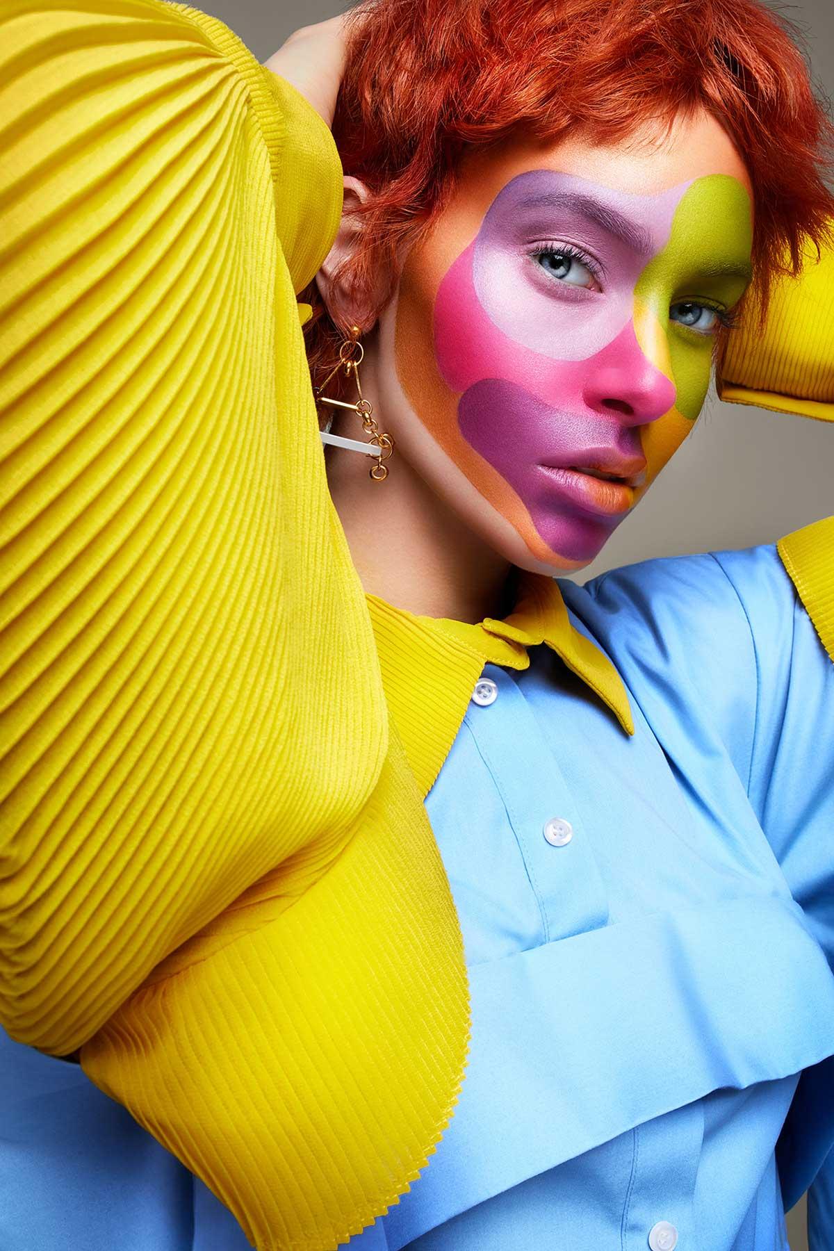 Retrato de mujer con maquillaje multicolor posa frente a la cámara.