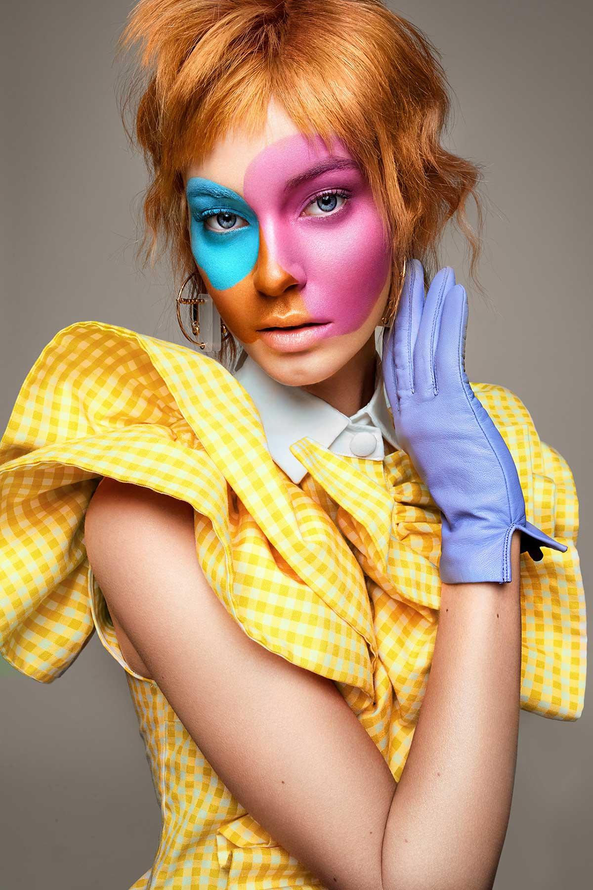 Retrato de mujer con vestido amarillo y guante azul con maquillaje multicolor.