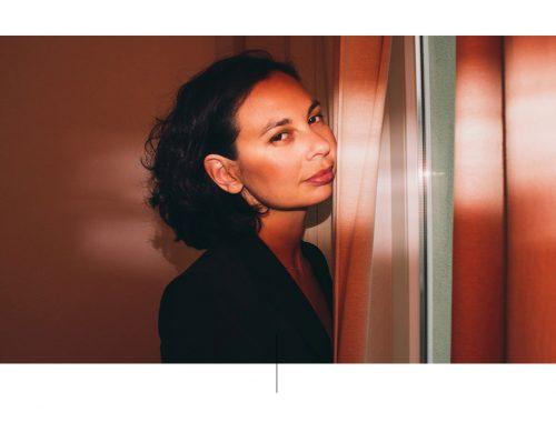 Retrato de mujer con blusa negra en habitación color coral.