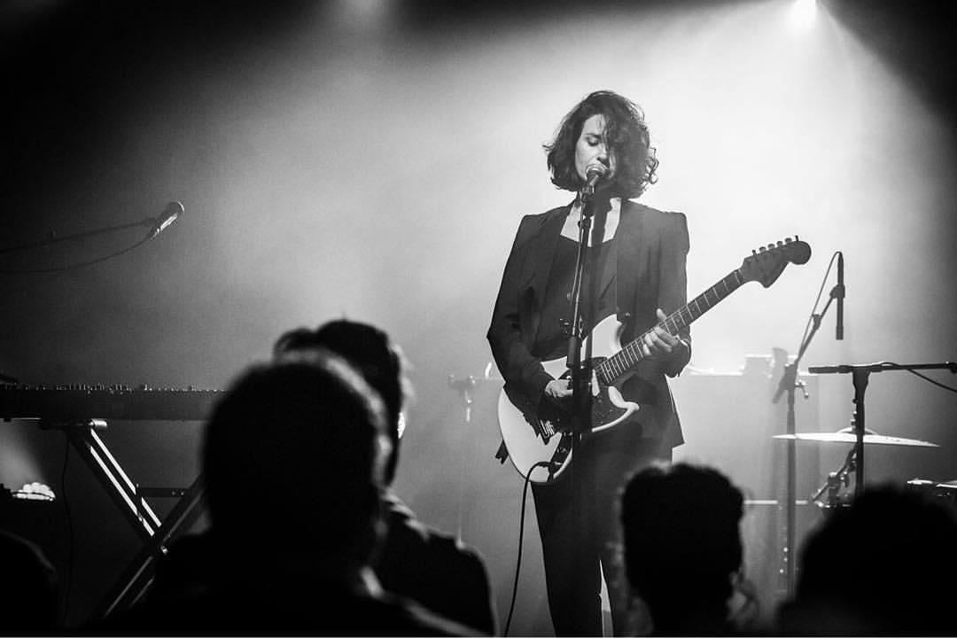 Imagen en blanco y negro de mujer con guitarra eléctrica sobre un escenario.