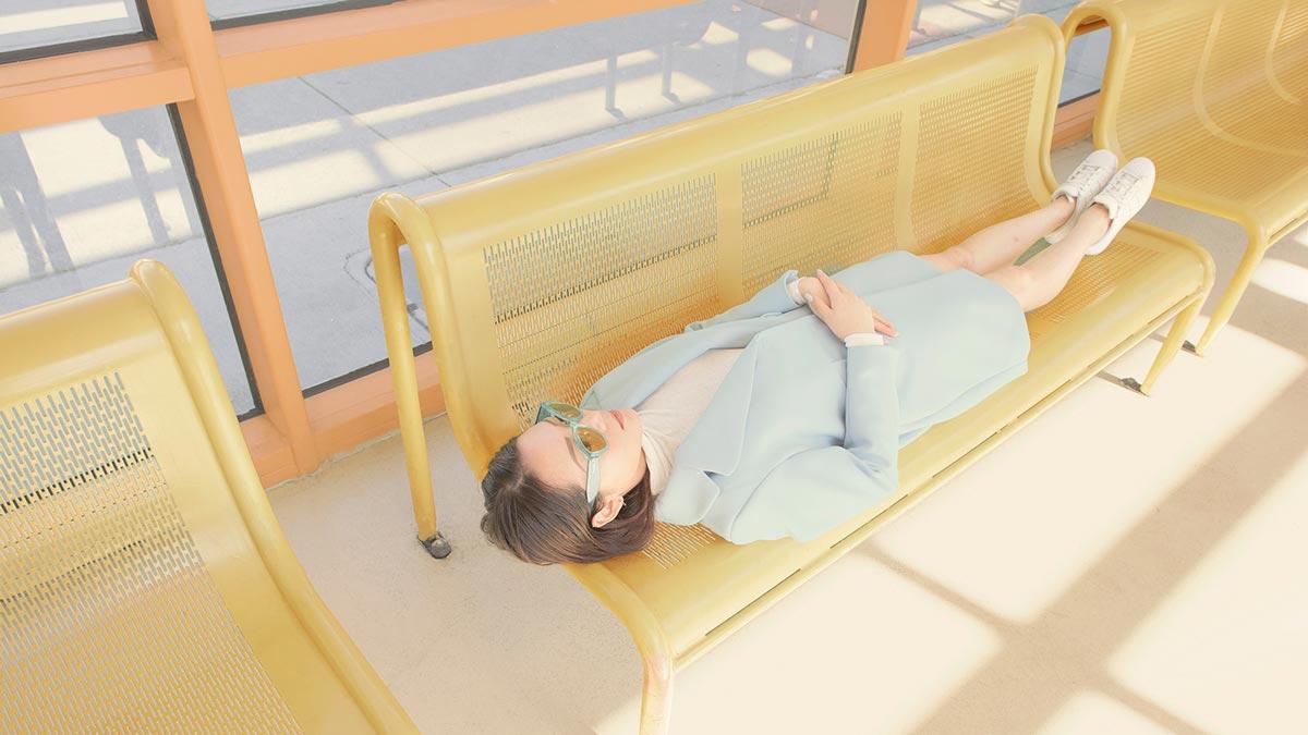 Γυναίκα που ξαπλώνει σε κίτρινο πάγκο.