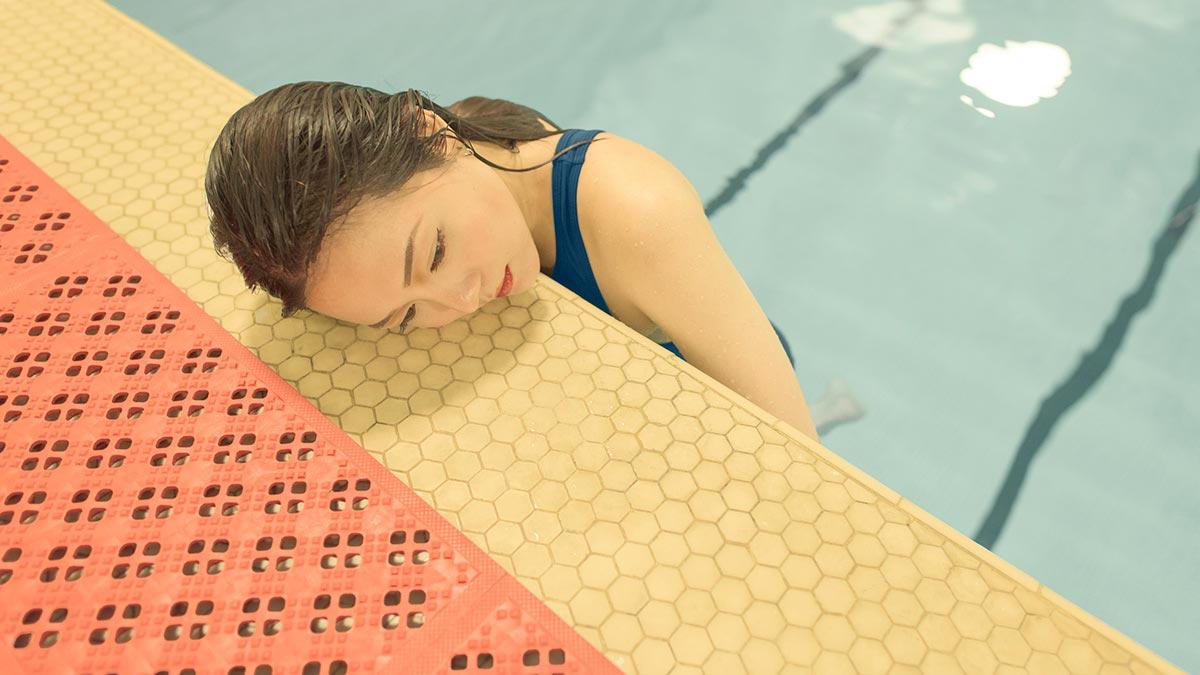 Γυναίκα βυθισμένη σε μια πισίνα με το κεφάλι της να στηρίζεται στην επιφάνεια.