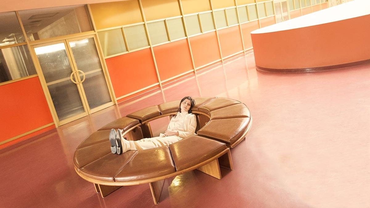 Γυναίκα που ξαπλώνει με τα πόδια της στην καρέκλα κυκλική καφέ,