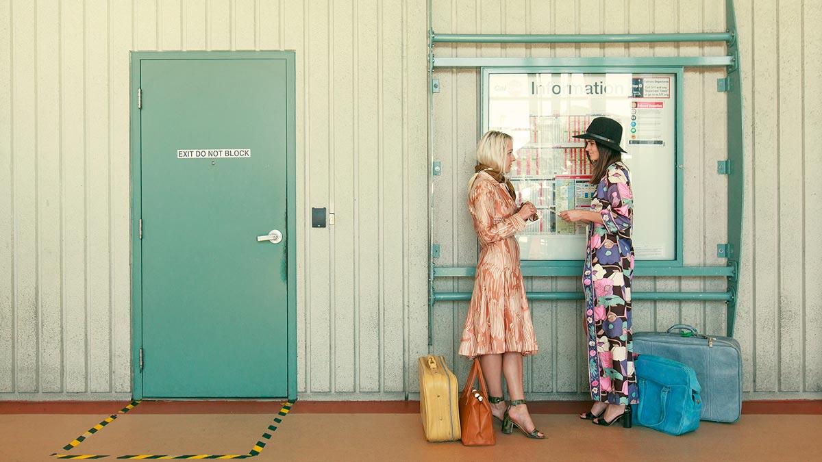 एक खिड़की के सामने सूटकेस के साथ दो महिलाओं की तस्वीर।