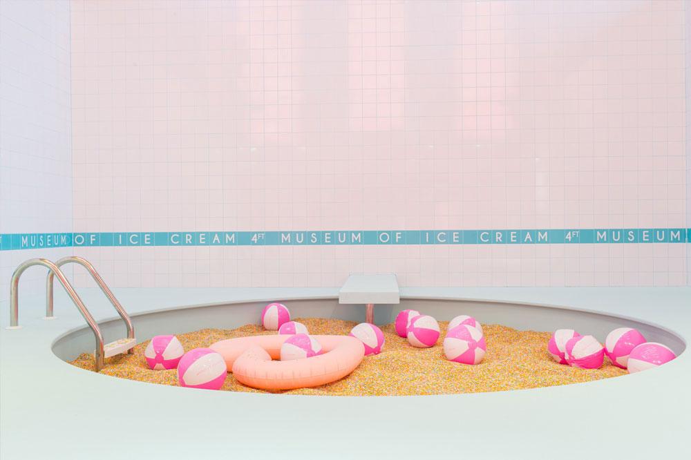 Alberca de trocitos de galleta con pelotas de playa color rosa y blanco.