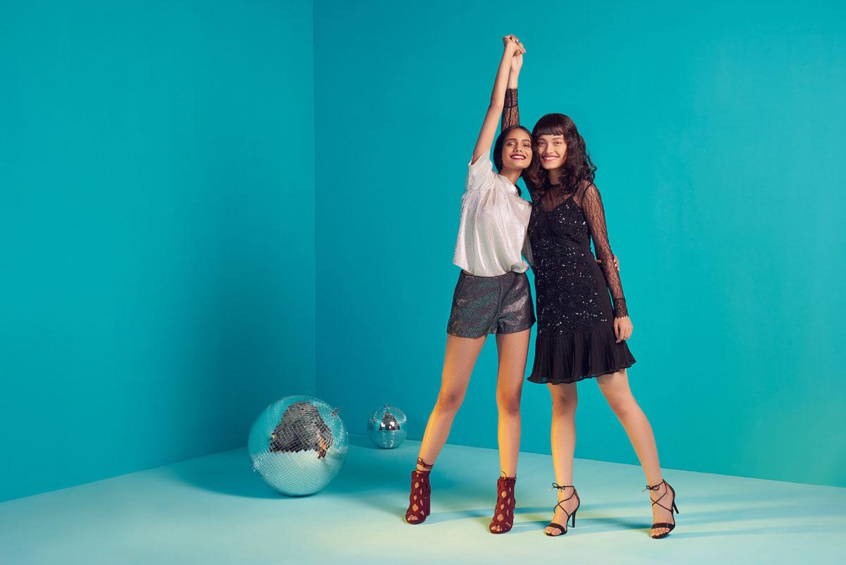Bilde av to kvinner som holder hender foran blå veggen.