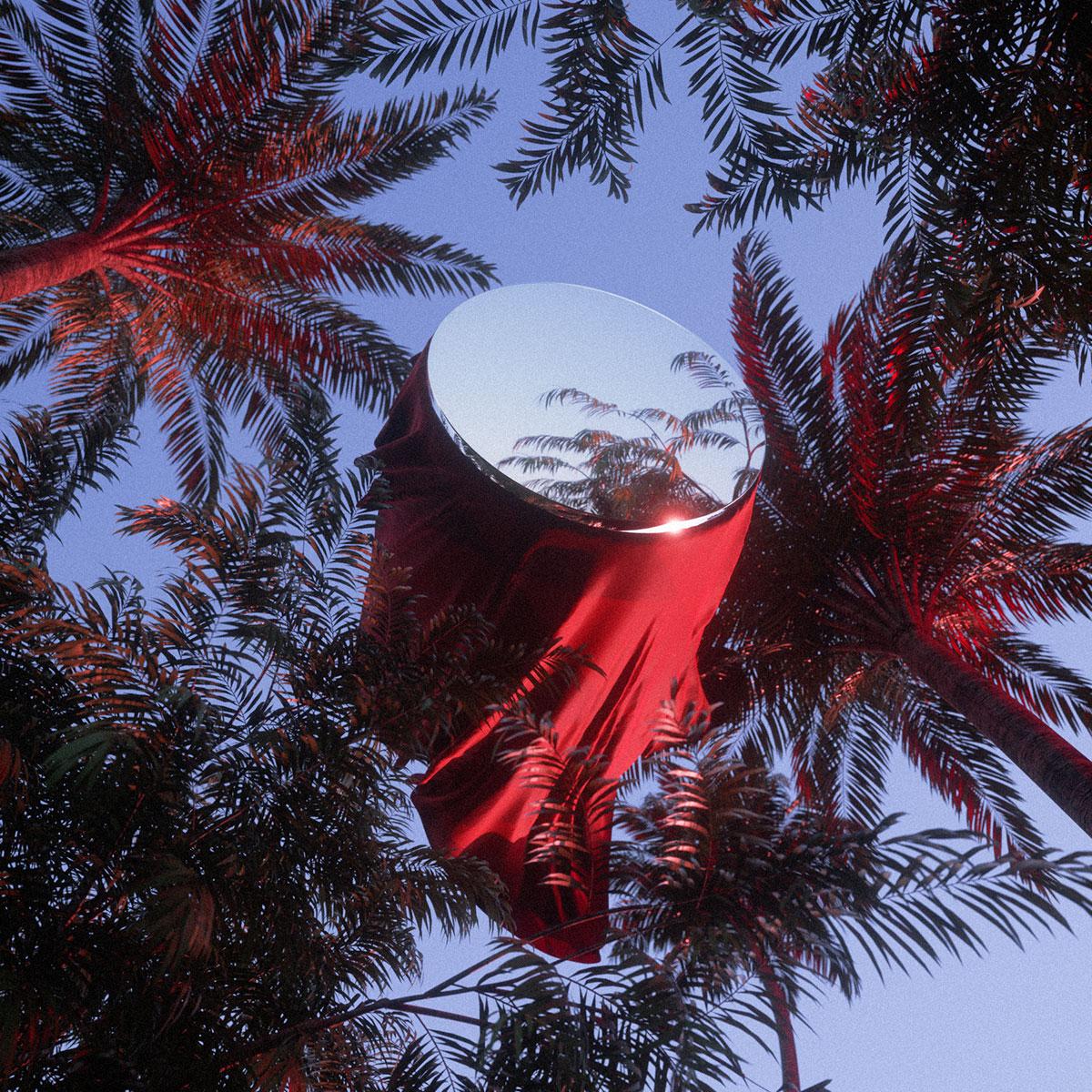 Escultura de espejo con tela roja entre palmeras del artista Mathieu L.B.