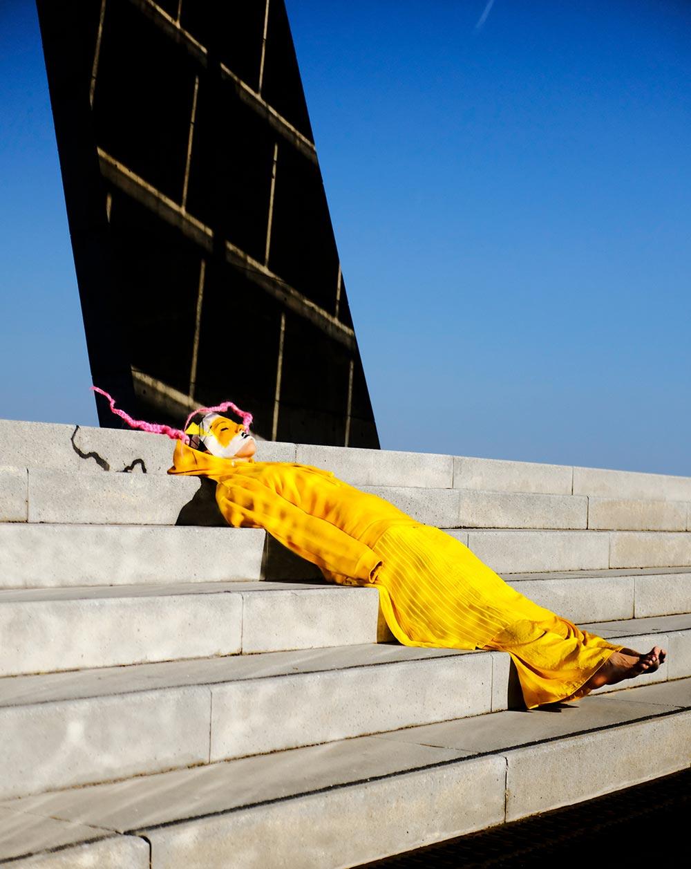 Kvinne i gul kjole som ligger på trappene.