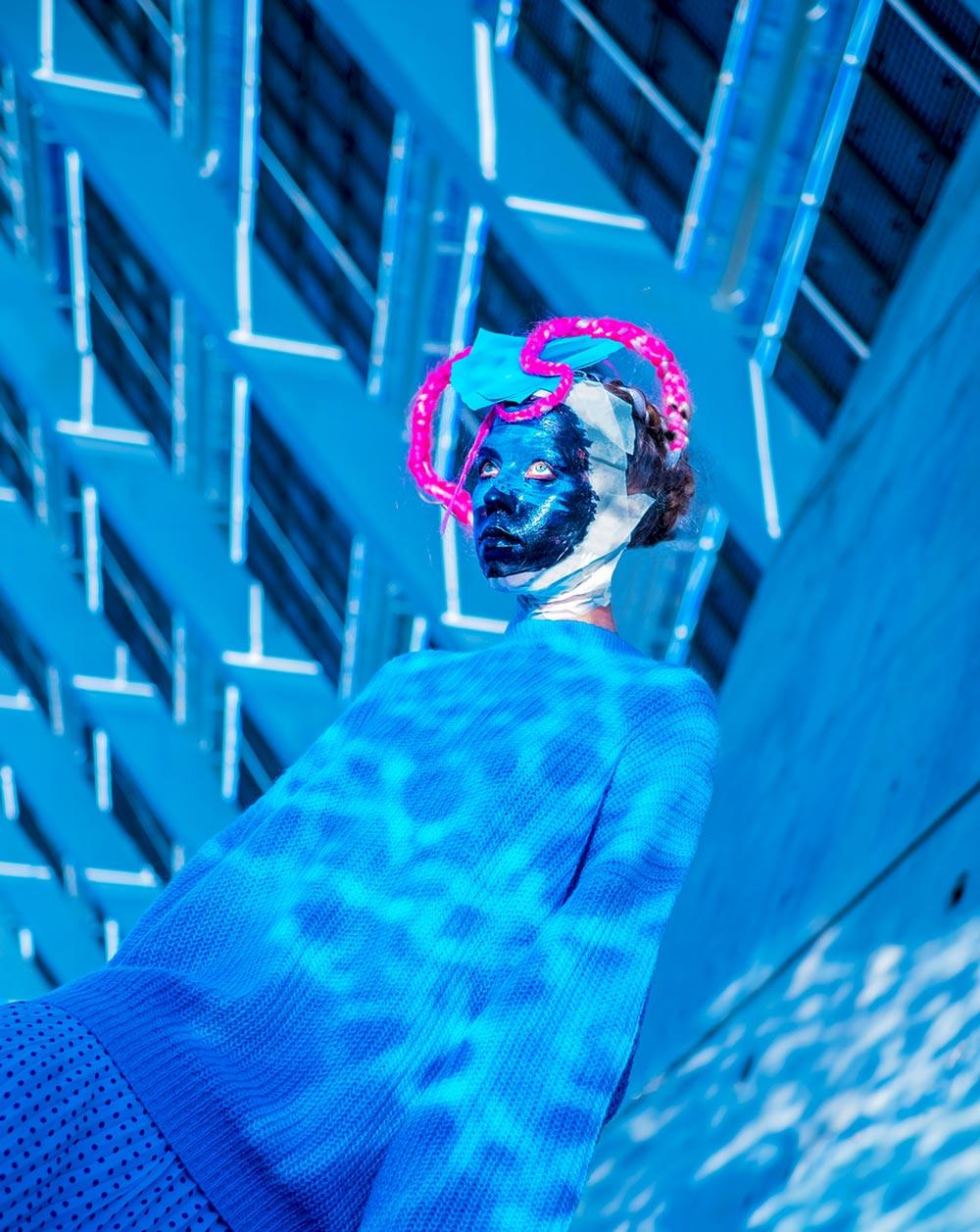 Kvinne på opplyst overflate med blått lys og rosa ornament på hodet.