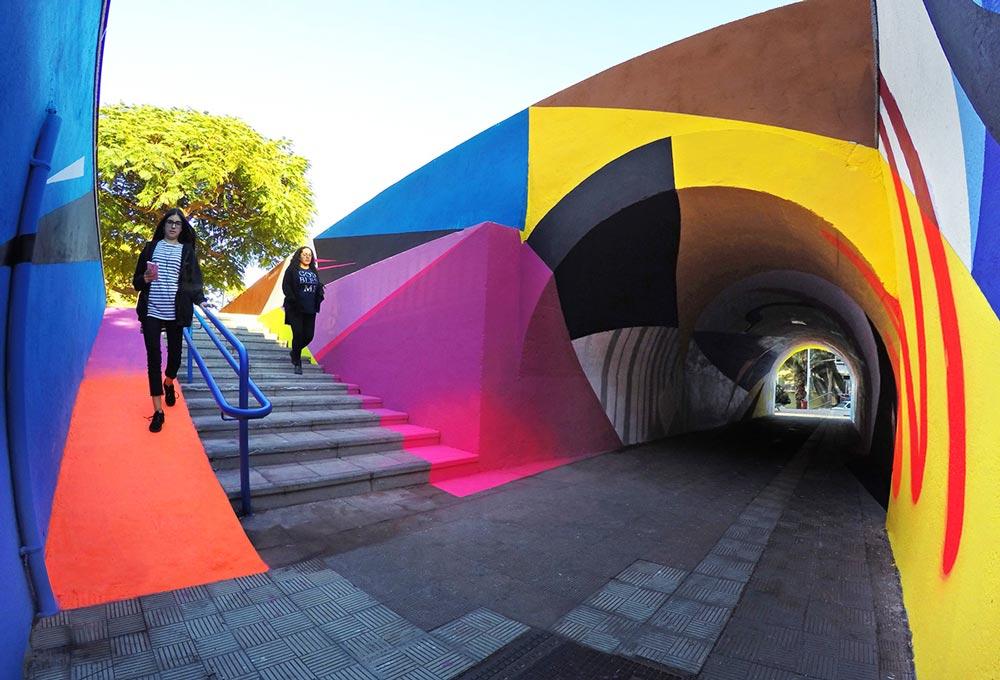 To kvinner går ved siden av tunnelen intervensert av kunstneren Lauro Samblás.