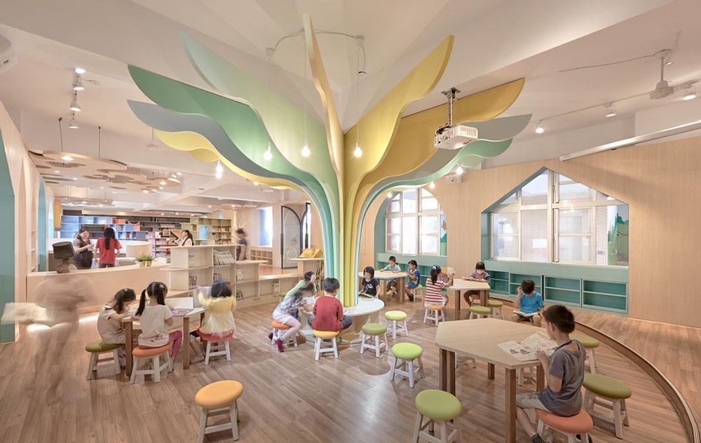 Εσωτερικό της βιβλιοθήκης Talispace με πίνακες και αναγνώστες παιδιών.