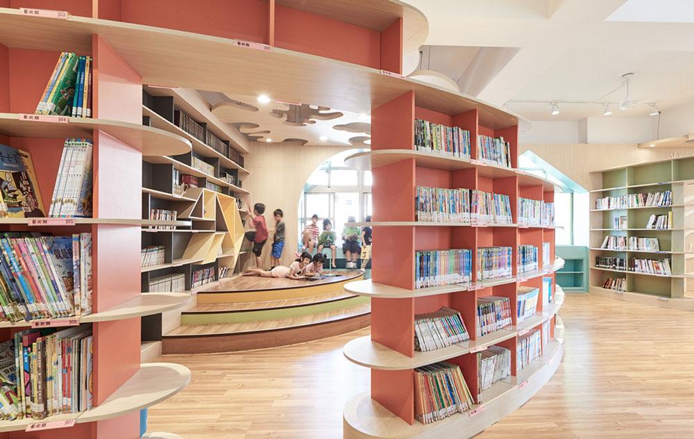 Κόκκινη ημικυκλική βιβλιοθήκη με παιδιά στο παρασκήνιο.