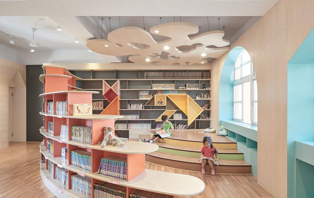 Πορτρέτο των παιδιών που διαβάζουν στις ξύλινες σκάλες μεταξύ βιβλιοπωλών.