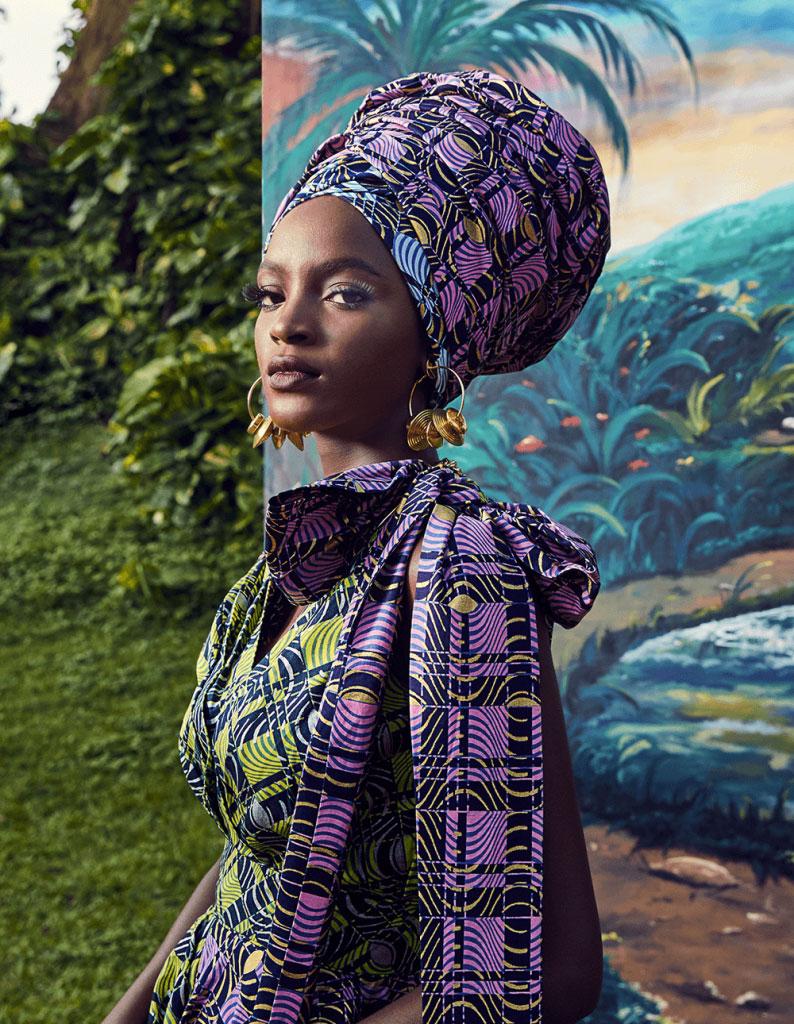बैंगनी पगड़ी और एक ही रंग के सूट के साथ महिला का चित्रण।
