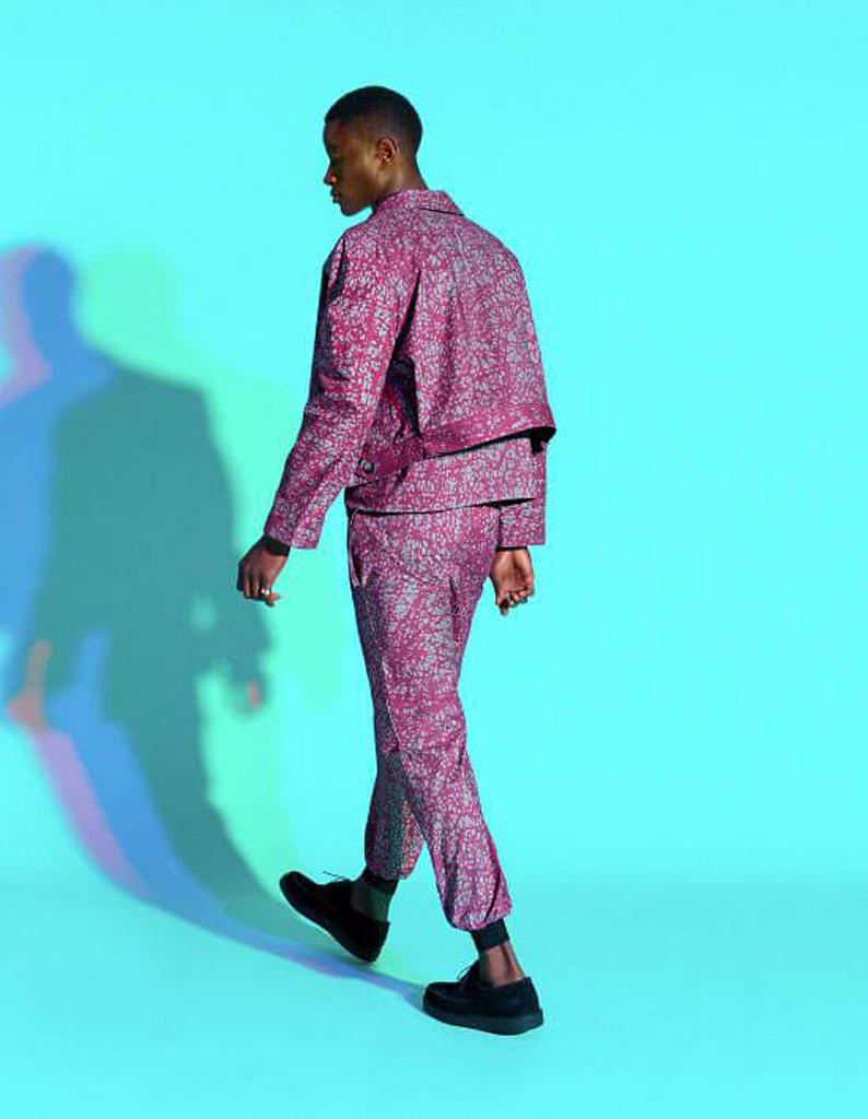पैटर्न वाले सूट और नीली पृष्ठभूमि के साथ चलने वाले आदमी की तस्वीर।