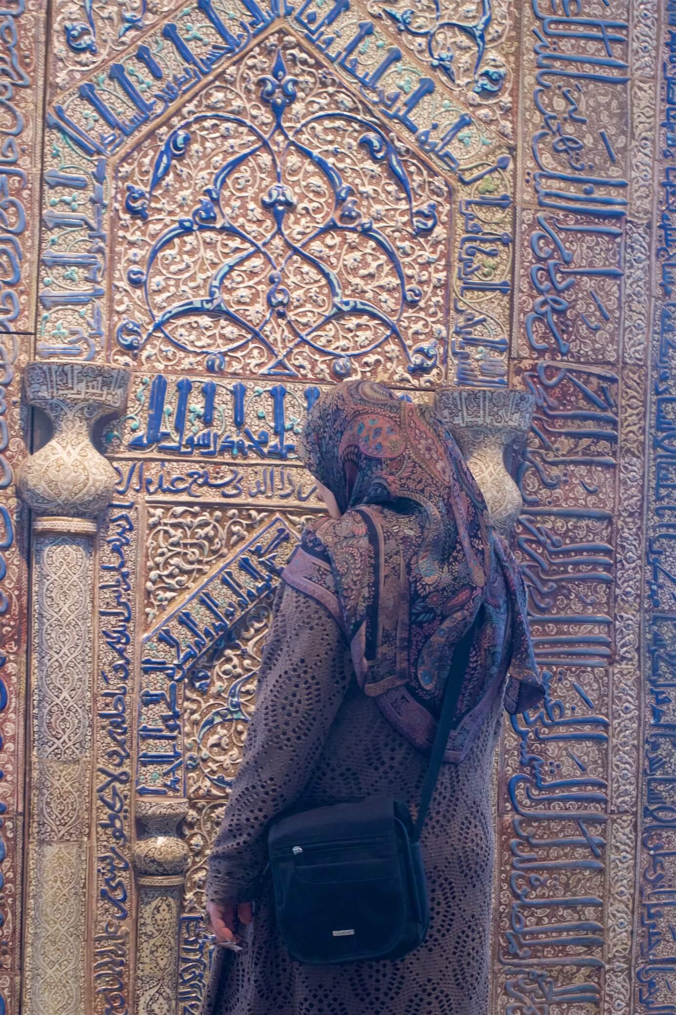 क्लासिक कला सजावट के साथ दीवार के सामने महिला।