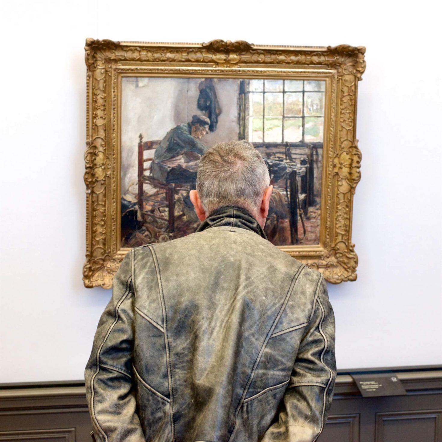 ग्रे जैकेट वाला आदमी कला का काम देखता है।