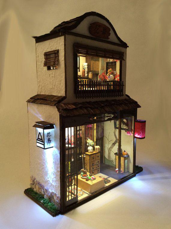 Casa en miniatura con muebles pequeños y lamparita.