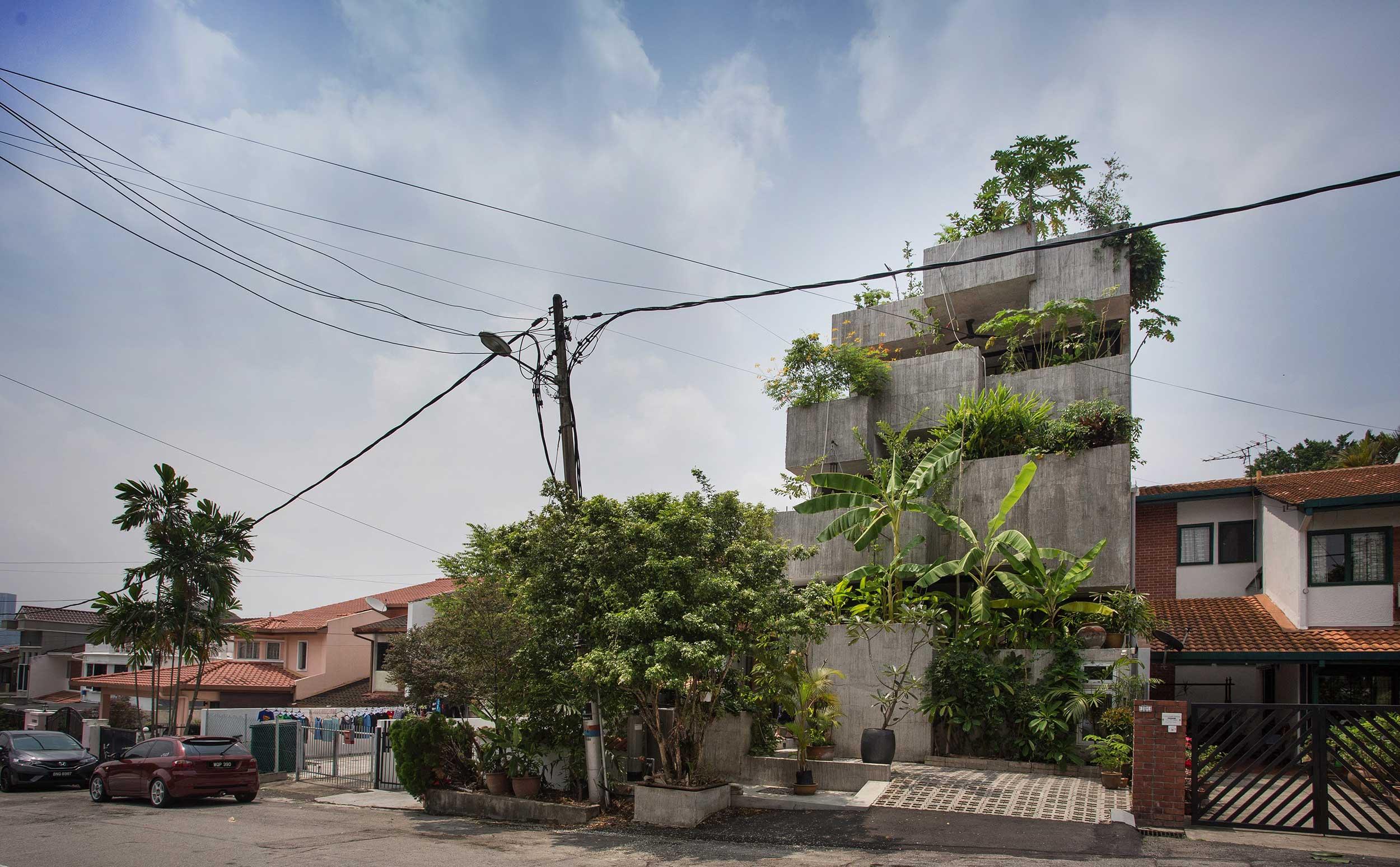 Γκρίζο κτίριο με πολλή βλάστηση σε όλα τα επίπεδα.