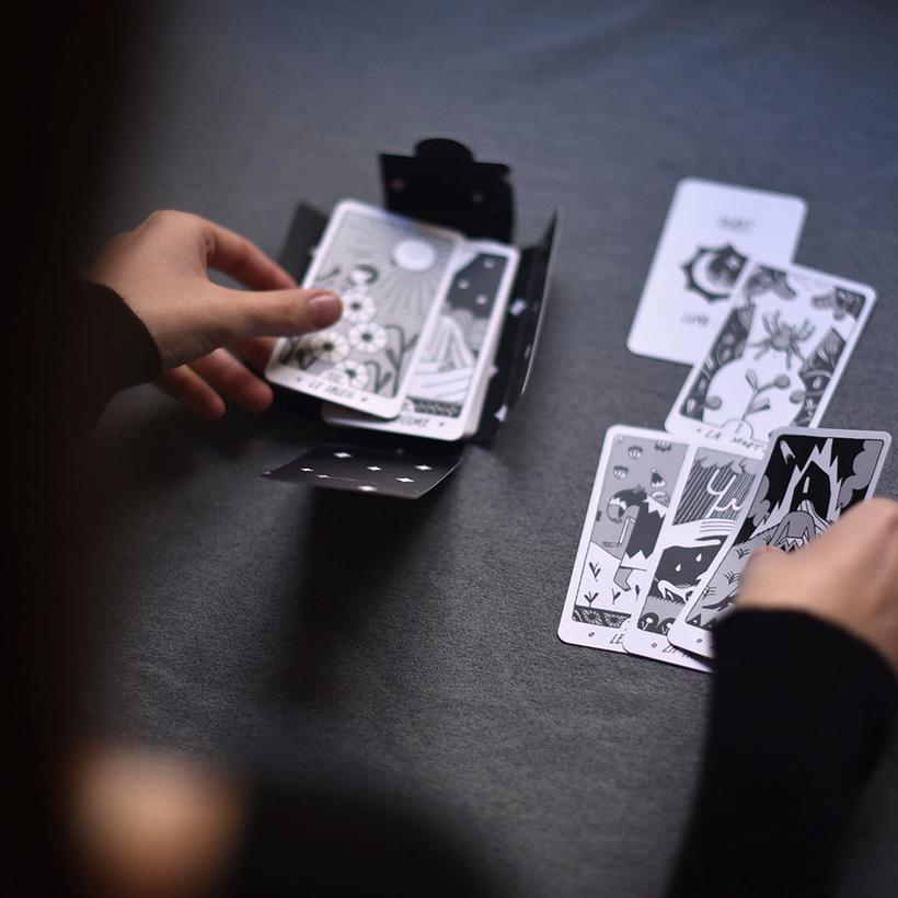 Mujer sosteniendo cartas de tarot diseñadas por Lunapan