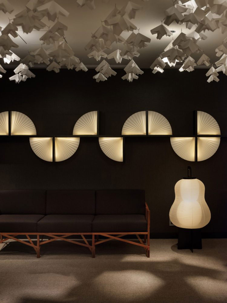Habitación con techo decorado con figuras blancas, lámparas en forma de abanico y un sillón café.
