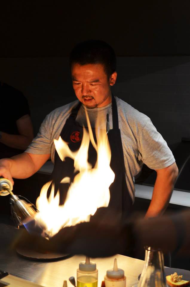 Chef con mandil negro prepara platillo japonés