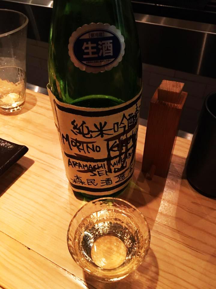 Botella de bebida japonesa y vaso sobre mesa de madera