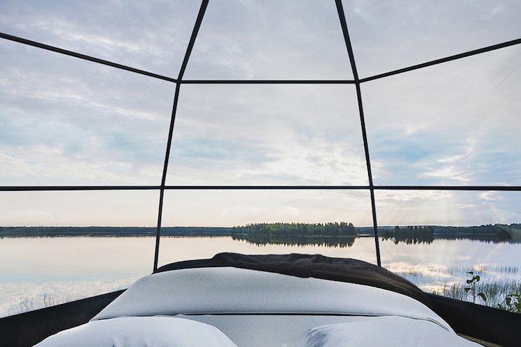 Vista del interior de una habitación con pared de vidrio y paisaje natural al fondo.