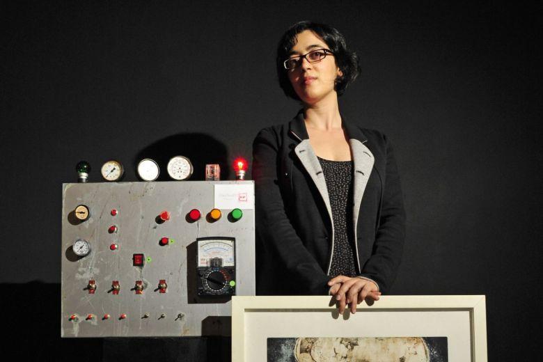 कलाकार लुसी लियू का एक काम पकड़े हुए काले सूट में महिला