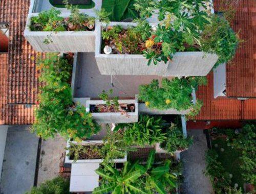 पौधों से भरी बालकनियों के साथ इमारत का हवाई दृश्य।