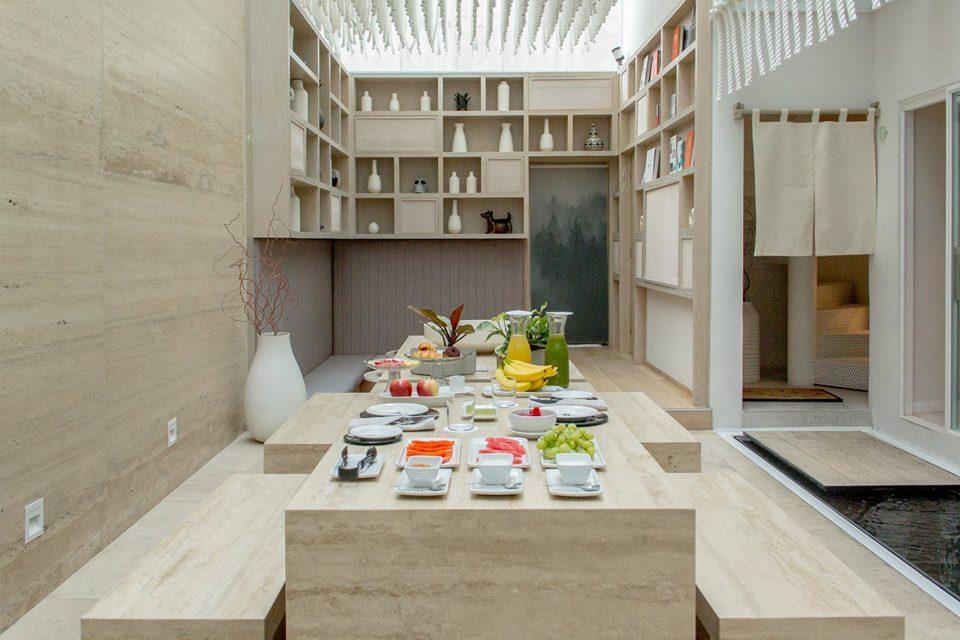 Mesa de restaurante con platillos de desayuno y jarras de jugo