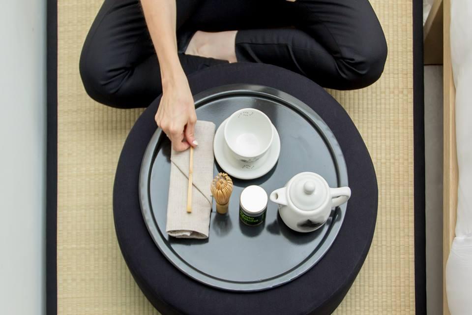 चाय के साथ टेबल के सामने पार पैरों के साथ व्यक्ति