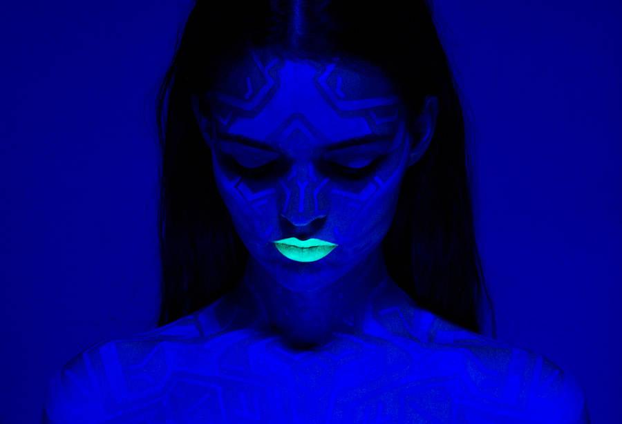 Retrato de mujer con iluminación azul y labios color fosforescente.