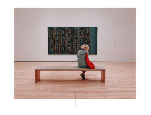 Γυναίκα με γκρι μπλούζα που κάθεται σε πάγκο μουσείο