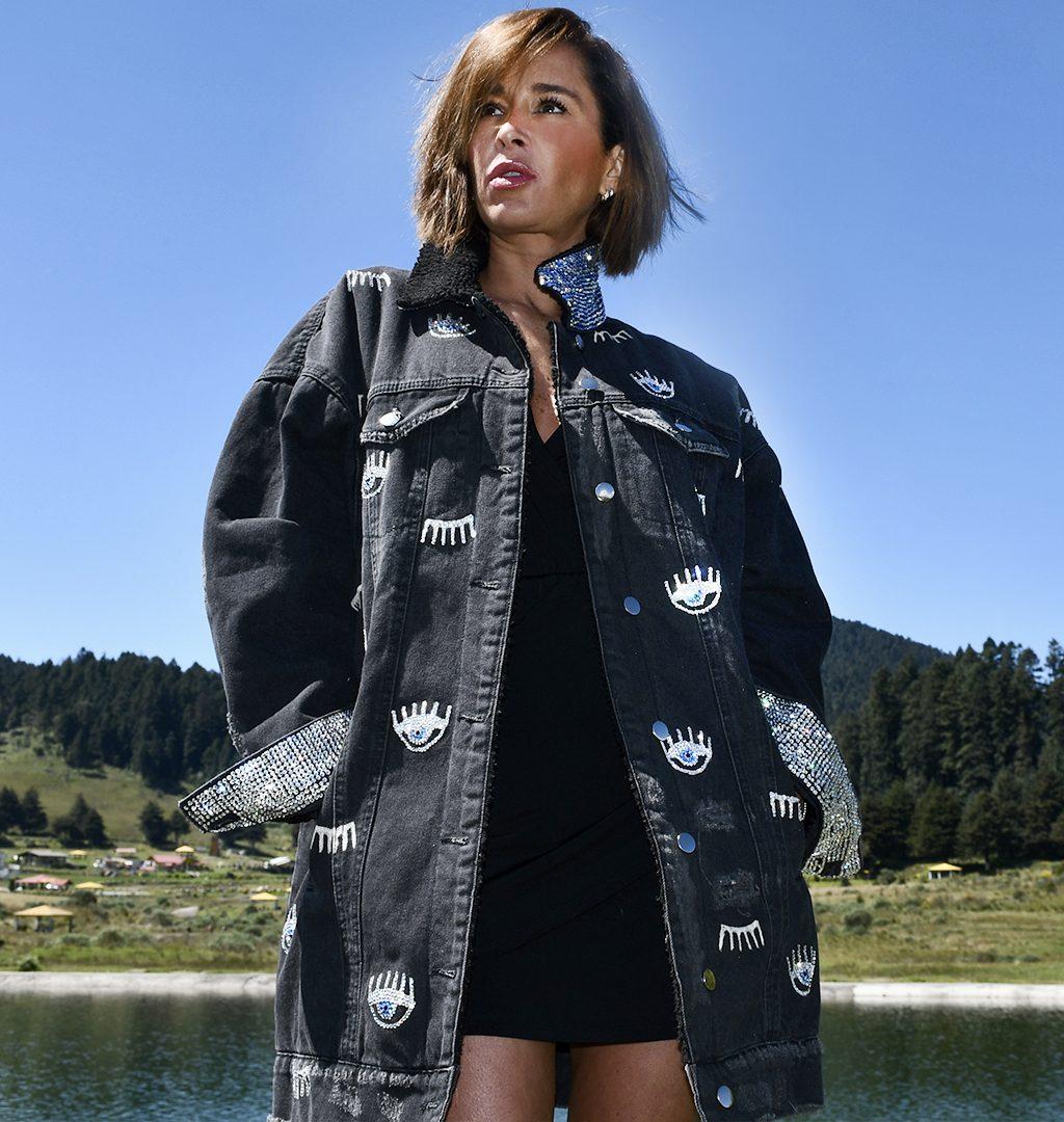 Kvinnemodell bærer en jakke med smykker inlays på nakke og ermer.