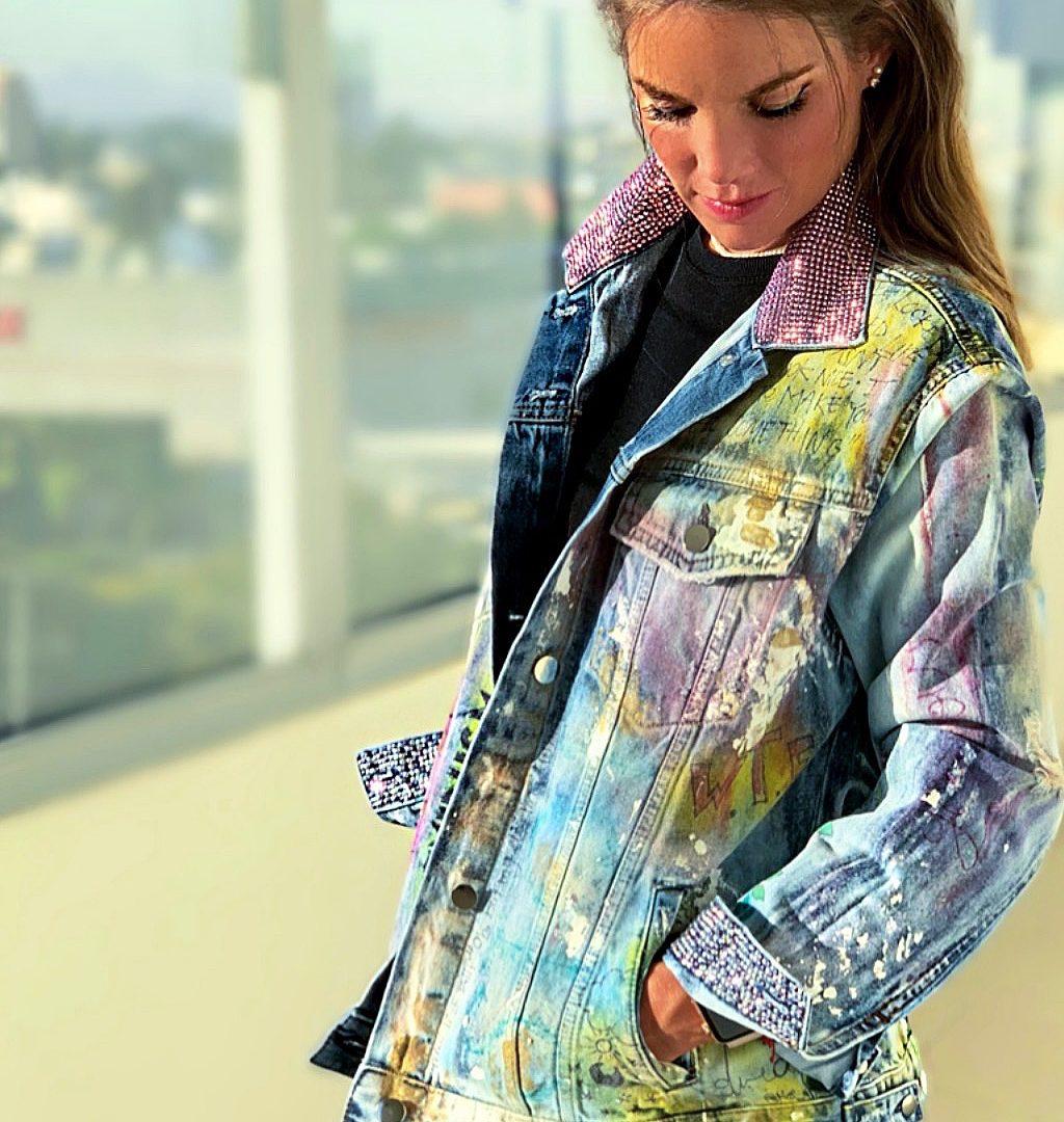 Kvinne iført en svart bluse og blå, rosa og gul denimjakke.