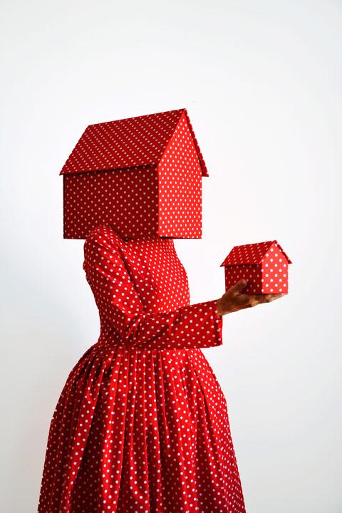 Vrouw in rode jurk en witte polka dots houdt in haar hoofd en rechterhand een klein huis.