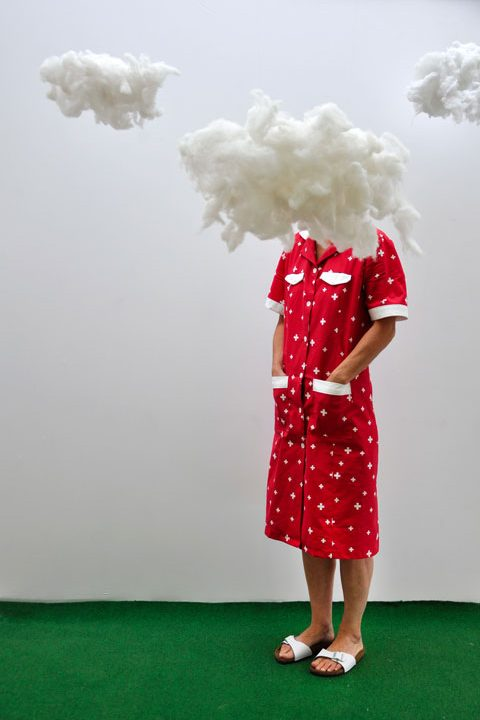 Vrouw met rode jurk en hoofd tussen de wolken.