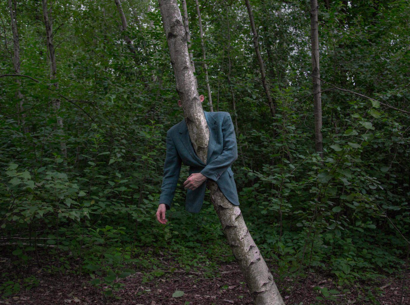 Hombre en bosque con un tronco