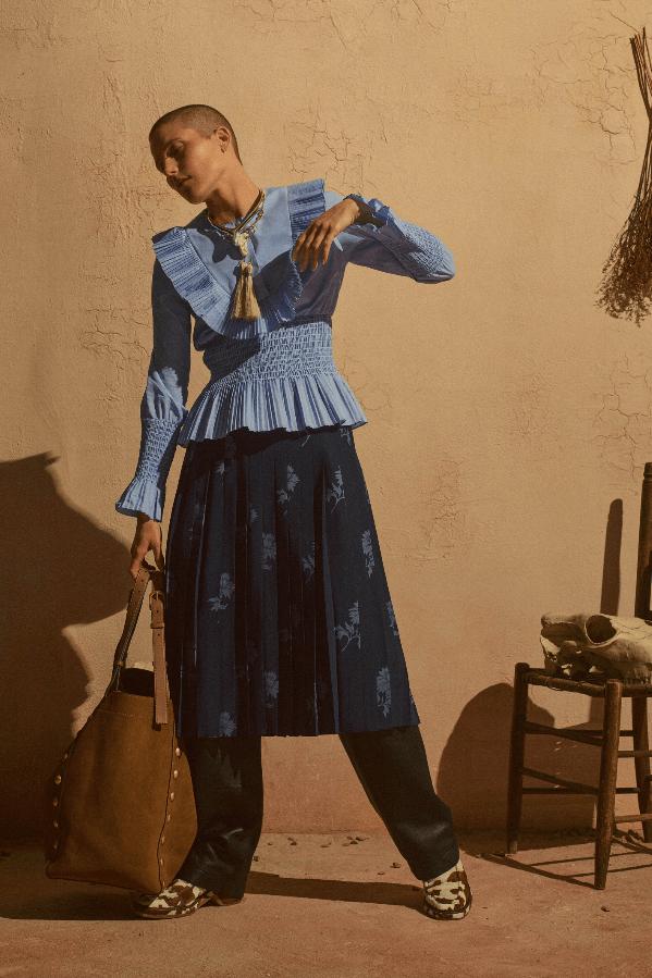 modell med blå bluse og faux conjuntiode
