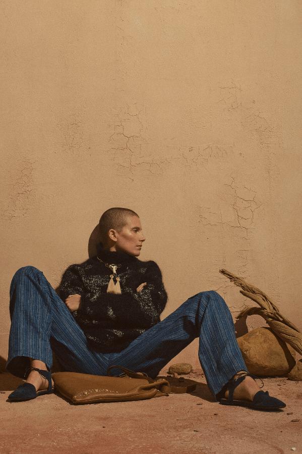 Sittende modell med svart jakke og blå bukser