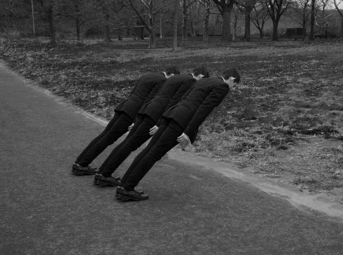 Tres hombre inclinados en la calle
