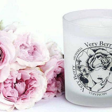Ροζ λουλούδια με ποτήρι κεριών