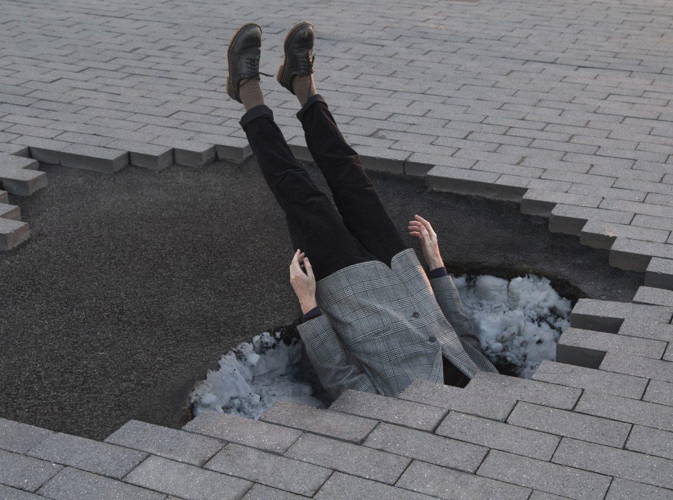 Hombre sumergido en el pavimento