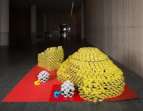 Escultura con latas de un carro amarillo
