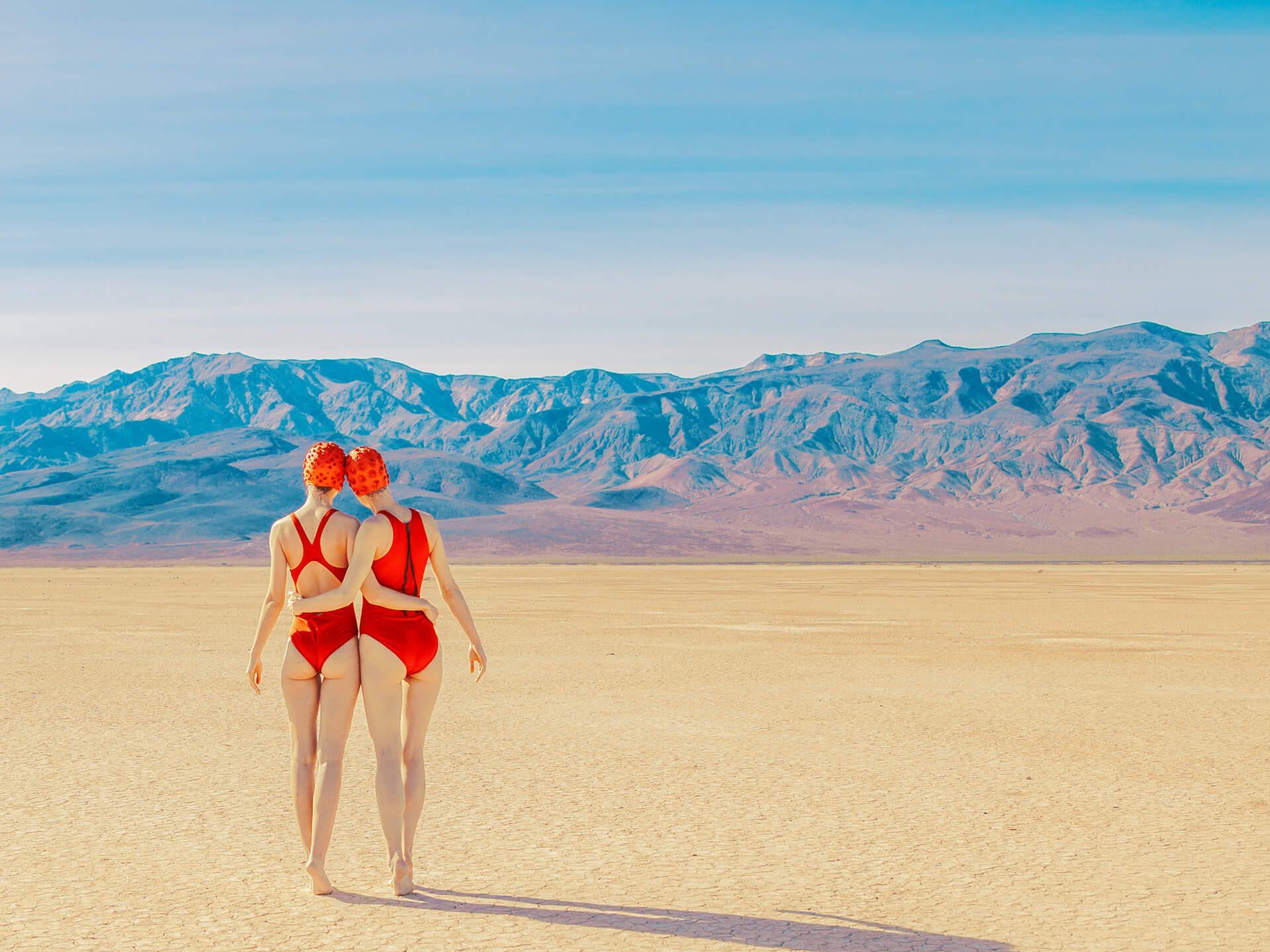 Jenter med badedrakter går på sanden