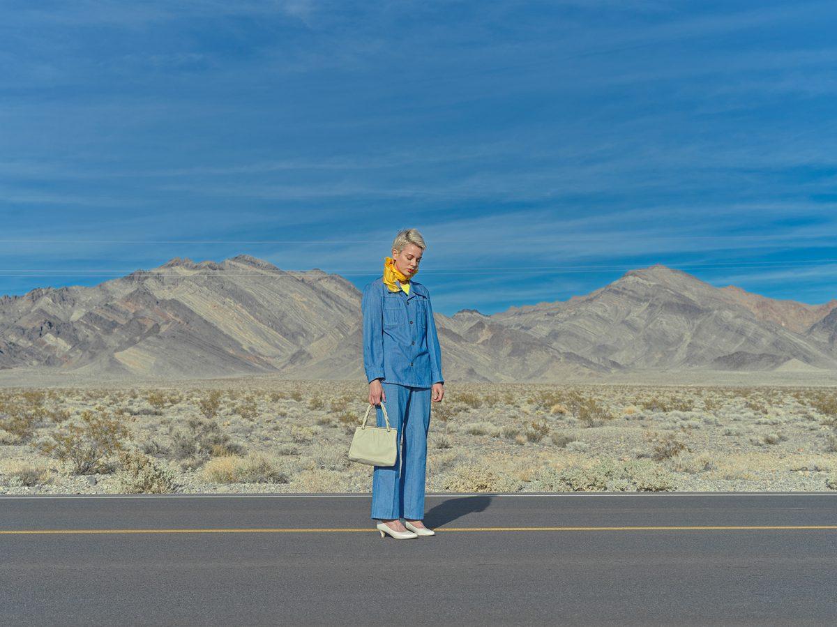 Jente med blå dress og pose på veien