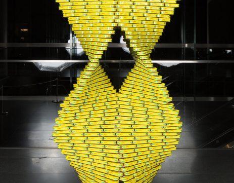 Escultura con latas de torre amarilla