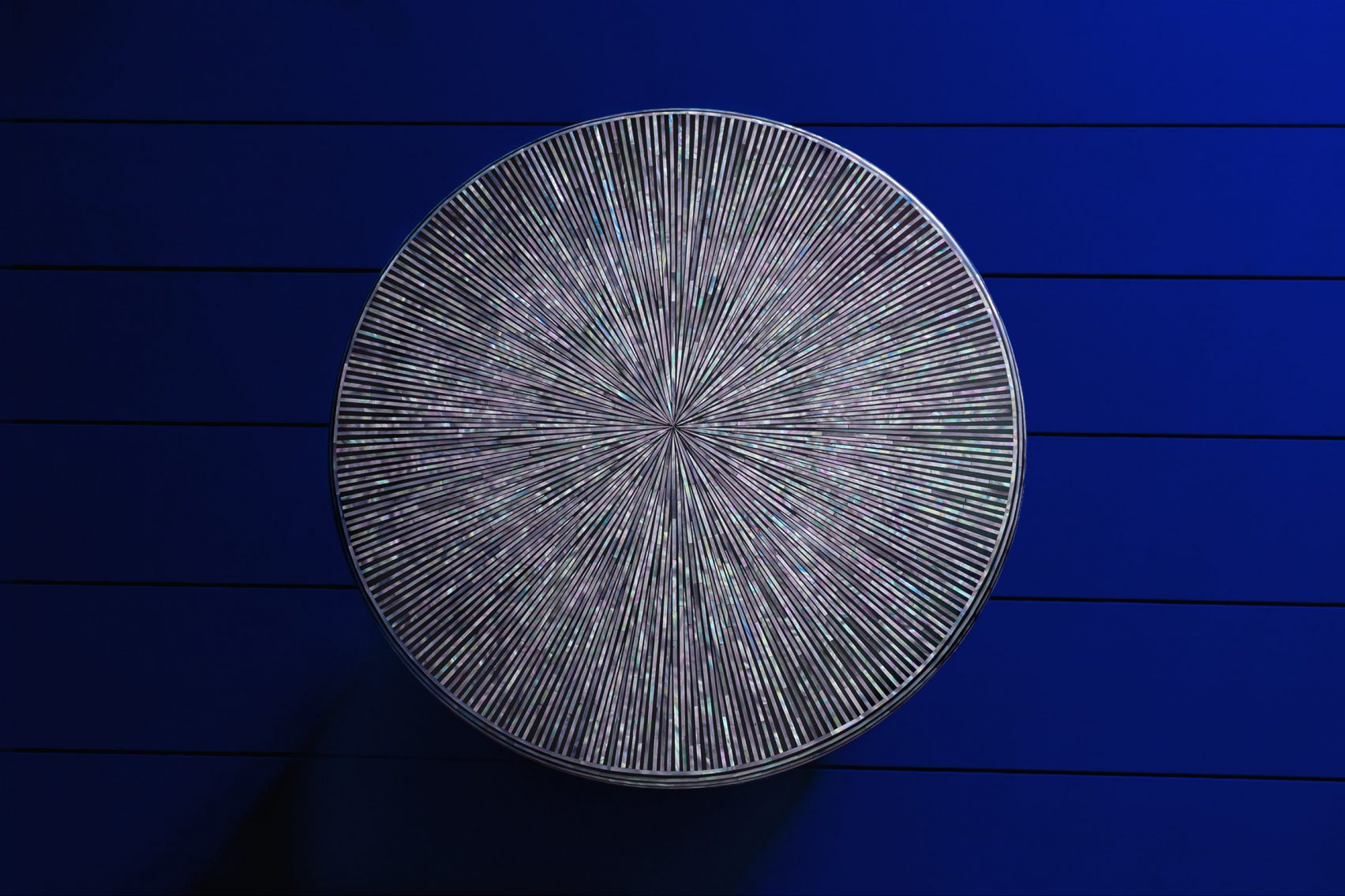 Base de mesa hecha de plumas e hilos de concha nacar